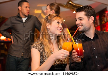 Young happy couple drinking cocktails in bar or restaurant, friends are standing in the background - stock photo