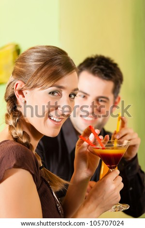 Young happy couple drinking cocktails in bar or restaurant; presumably it is a first date - stock photo