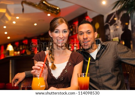 Young happy couple drinking cocktails in bar or restaurant, presumably it is a first date - stock photo