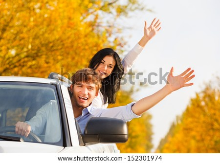 young happy couple driving in car. excited couple on road trip in new car. holding hands up open palm at you - stock photo