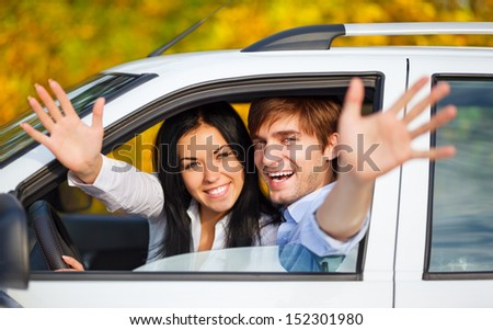 young happy couple driving in car. excited couple on road trip in new car. holding hands up open palm at you