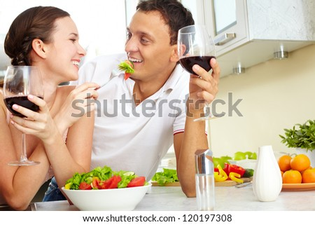 Young happy couple eating vegetable salad and drinking red wine