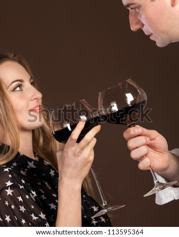 Young happy couple enjoying a glasses of red wine. Focus on glasses - stock photo