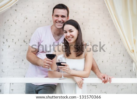 Young happy couple enjoying a glasses of red wine on terrace
