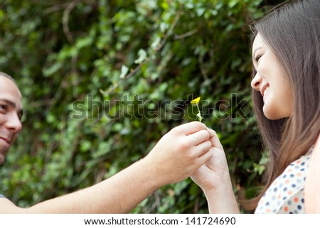 Young happy couple enjoying each others company outdoors.  The man is giving a flower to his love interest. - stock photo