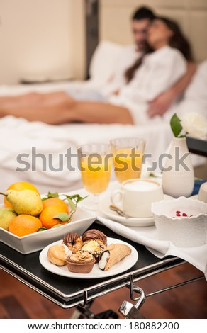 Young happy couple having breakfast in luxury hotel room. Shallow depth of field. - stock photo
