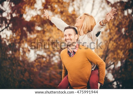 Young happy couple having fun in autumn park.