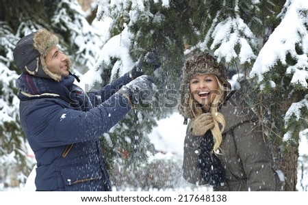 Young happy couple having fun in snowfall, smiling. - stock photo