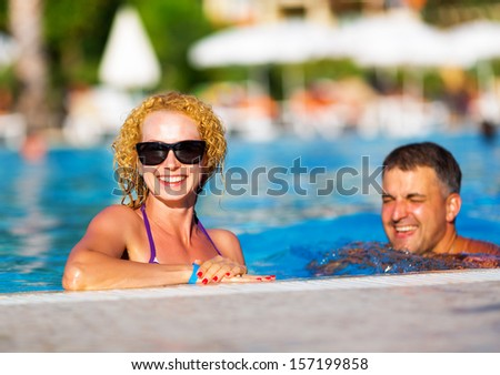 Young happy couple having fun in the pool - stock photo