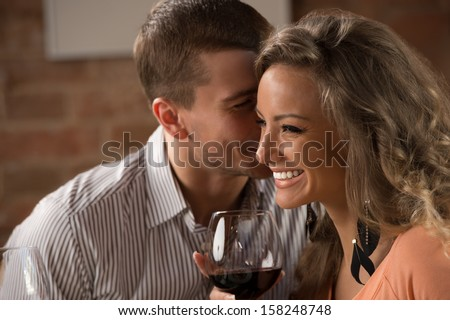 Young happy couple having romantic date at restaurant - drinking wine and eating gourmet food - stock photo
