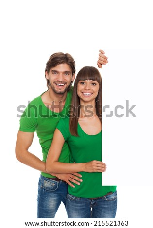 young happy couple hold blank board with empty copy space, man and woman smile, wear green t shirt isolated over white background