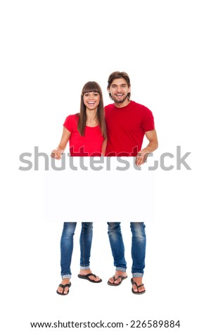 young happy couple hold blank board with empty copy space, man and woman smile, wear red shirt isolated over white background