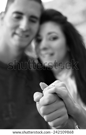 Young happy couple holding a diamond engagement ring.  Shallow depth of field with sharp focus on the ring. - stock photo