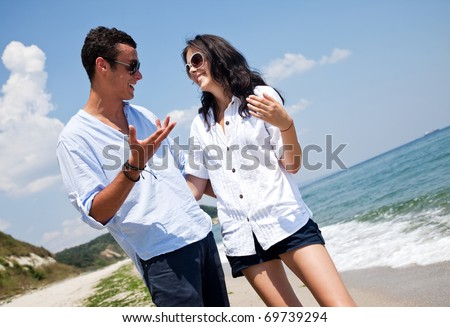 Young happy couple hugging and talking along a solitary beach