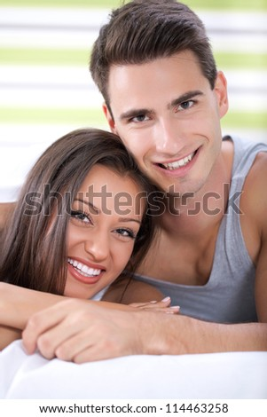 Young happy couple hugging in bed - stock photo