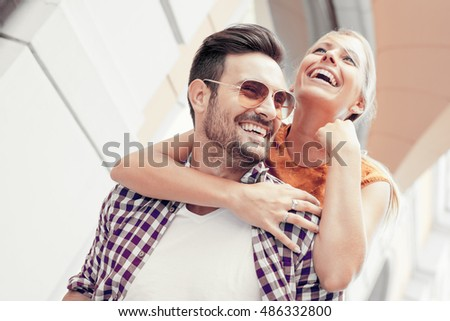 Young happy couple hugging on the city street.