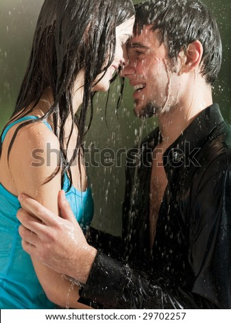 Young happy couple hugging under a rain - stock photo
