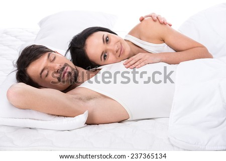 Young happy couple in a bed. Isolated on white background. - stock photo