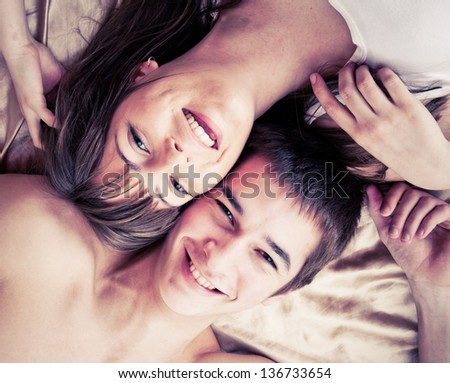 Young happy couple in bed - stock photo