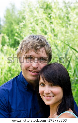 young happy couple in front of green background