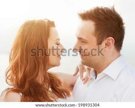 Young happy couple in love in a romantic moment of touching and looking in the eyes on the beach in summer sunshine.  - stock photo