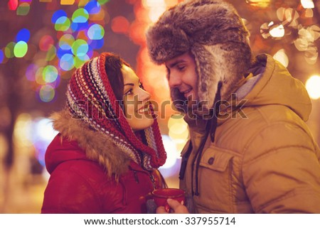 Young happy couple in love outdoor in evening Christmas lights - stock photo