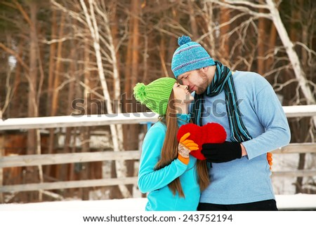 Young happy couple in love outdoors in the winter with a red heart in hands - stock photo