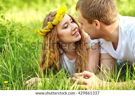 Young happy couple in love outdoors. loving man and woman lying in the grass
