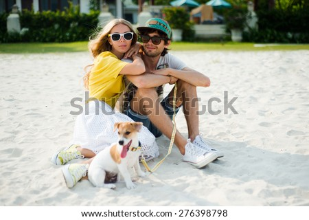 Young happy couple in love sitting on the beach in summer sunny evening, with dog. Summer mood,smiling and having fun during their vacation, wearing sunglasses, cap, yellow and printed shirt, romance  - stock photo