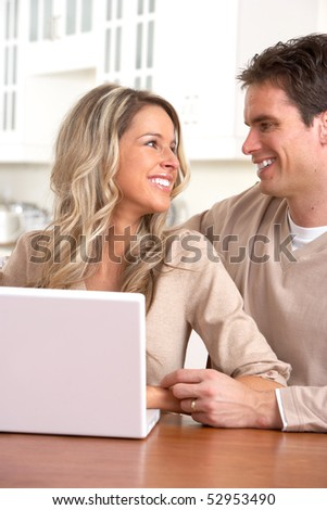 Young happy couple in love with laptop at home