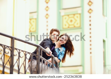 Young happy couple in the city. Young man and beautiful woman on street at dating. Two lovers in the city. Walking through the city day.  Love between two people. Honeymoon. Love story series - stock photo