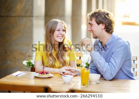 Young happy couple in the outdoor cafe  - stock photo