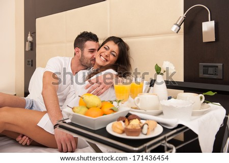 Young happy couple joking while having breakfast in luxury hotel room. - stock photo