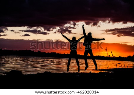 young happy couple jumping on beach
