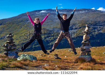 Young happy couple jumping on mountain background. - stock photo