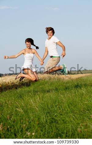 young happy couple jumping outside in summer on field - stock photo