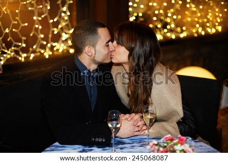 Young happy couple kissing at restaurant with glass of champagne on the table, celebrating valentine day kiss
