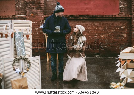 Young happy couple laughing and enjoying christmas street decorations with gifts in craft paper, cookies, cacao, handmade wooden table and red brick wall
