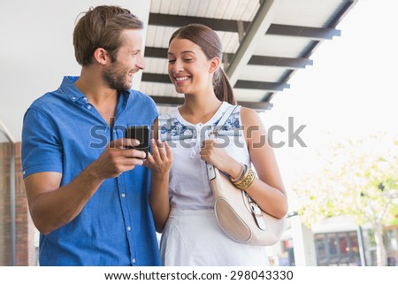 Young happy couple looking at mobile phone before shopping - stock photo