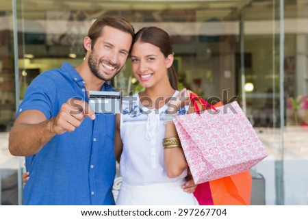 Young happy couple looking camera after shopping holding a credit card - stock photo