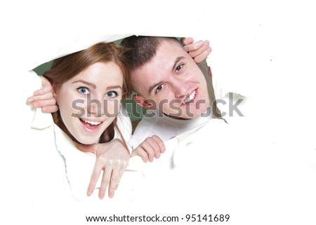 young happy couple looking out from hole in paper - stock photo