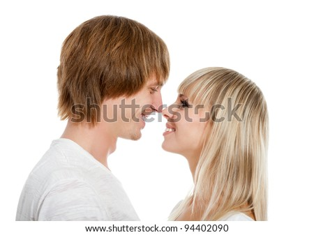 Young happy couple love smiling, looking to each other and hug kiss touching nose, isolated over white background - stock photo