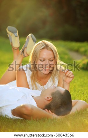 Young happy couple lying down on grass in the sun