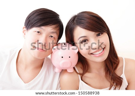 young happy couple lying in a bed with pink piggy bank, asian family - stock photo