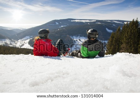 Young happy couple lying in snowy mountains, czech - stock photo