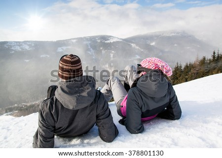 Young happy couple lying in snowy mountains, Jeseniky, Dolni Morava