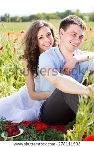 Young happy couple man and woman resting on a green meadow full of poppy flowers