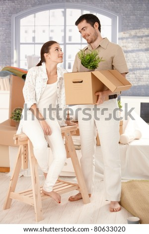 Young happy couple moving to new house, unpacking boxes, mess around, smiling.? - stock photo