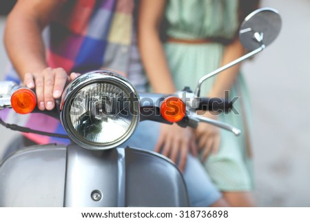 Young happy couple near the old retro scooter in a city street. Close up - stock photo