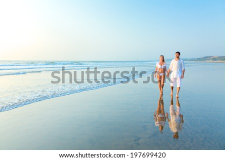 Young happy couple on a sea beach at sunset. India, state Goa - stock photo